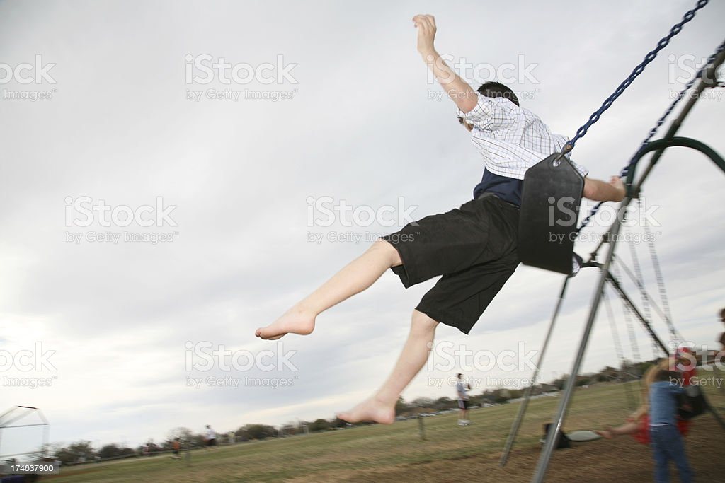 Young Boy Flying Off a Swing stock photo