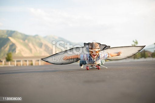 istock Young Boy Flying on Skateboard with Wings 1135838030