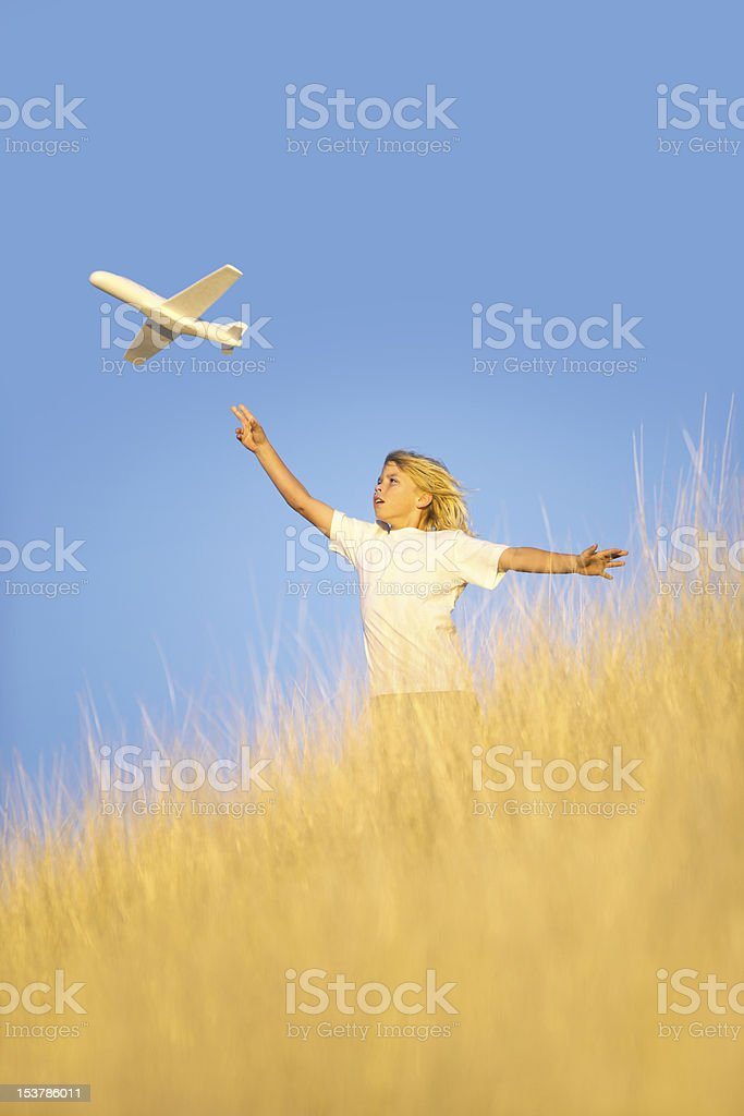 Young Boy Flying Toy Glider Airplane in Field royalty-free stock photo