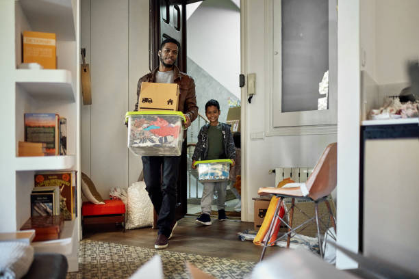 Young Boy Following Father into New Apartment on Moving Day stock photo