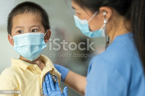 Young Asian boy receiving his annual checkup at the doctors. Both him and the female doctor are wearing masks due to the COVID-19 outbreak to avoid the transfer of germs.