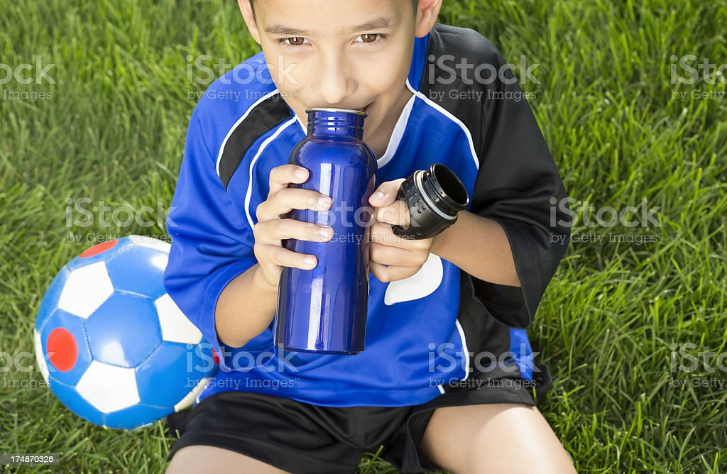 Young boy getting thirsty from playing soccer royalty-free stock photo