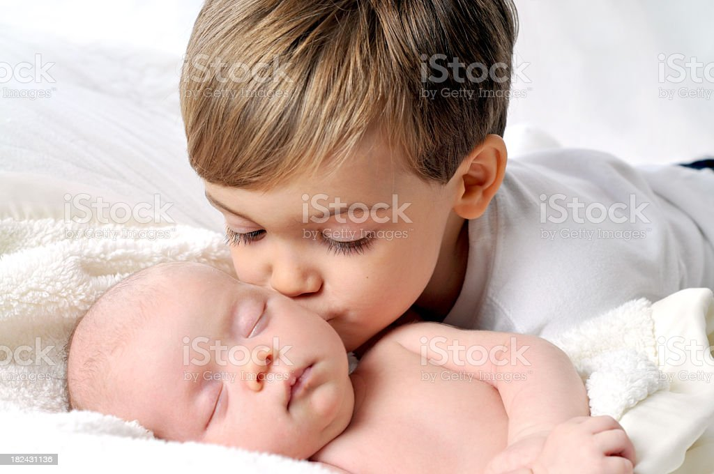 Young Boy Giving New Baby Sister a Kiss While Sleeping stock photo