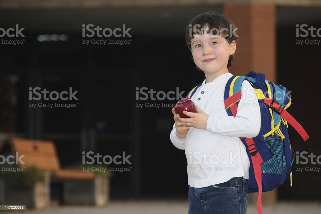 Young boy going back to school holding Apple stock photo
