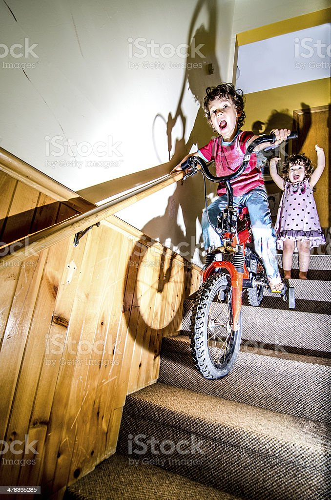 young boy going down the basement stairs on his bike stock photo