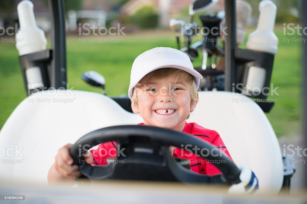 Young Boy Golfer In A Golf Cart stock photo