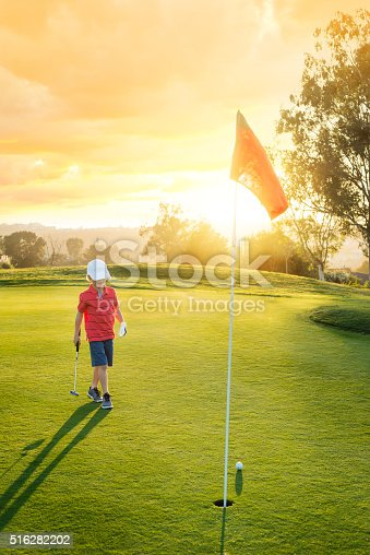 Young Boy Golfer Putting During Sunset