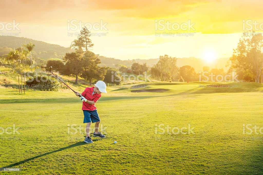 Young Boy Golfer Teeing Off During Sunset stock photo