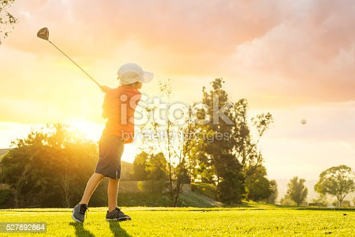 istock Young Boy Golfer Teeing Off During Sunset 527892864
