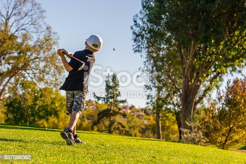 istock Young Boy Golfer Teeing Off During Sunset 637066362