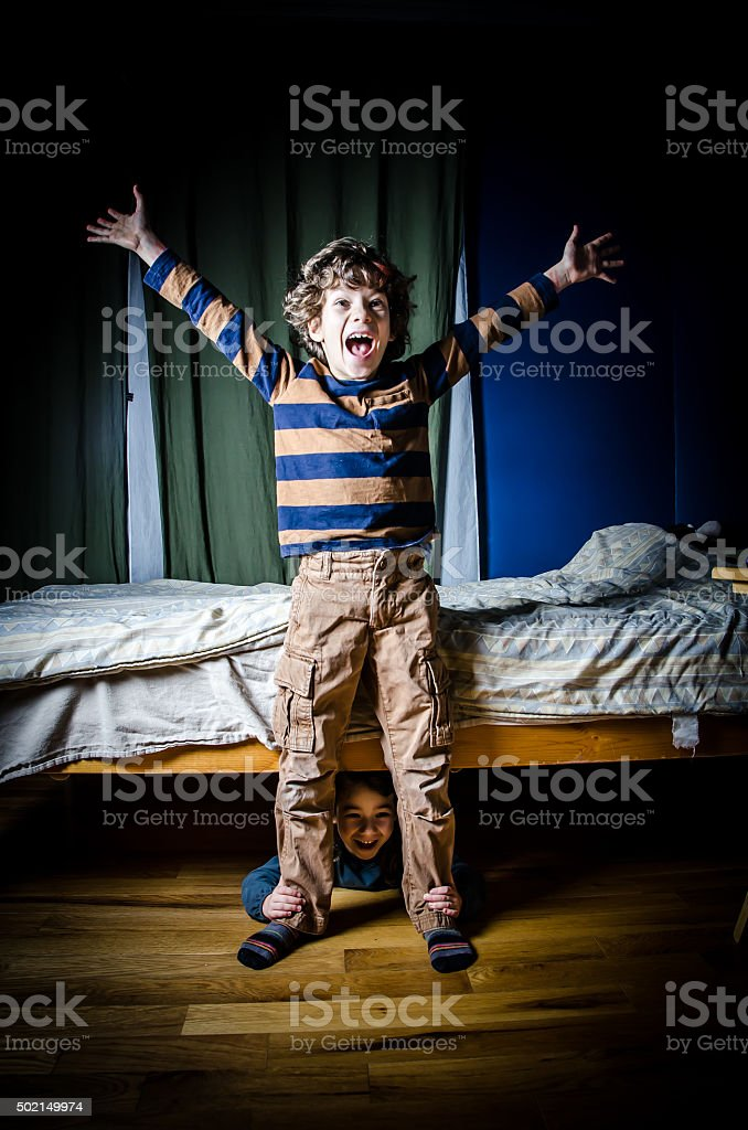 Young boy grabbed by his ankles by sister under bed stock photo