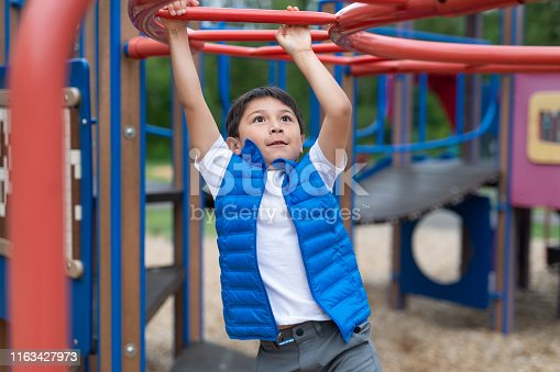 A young Native American boy swings his way across monkey bars at the playground.