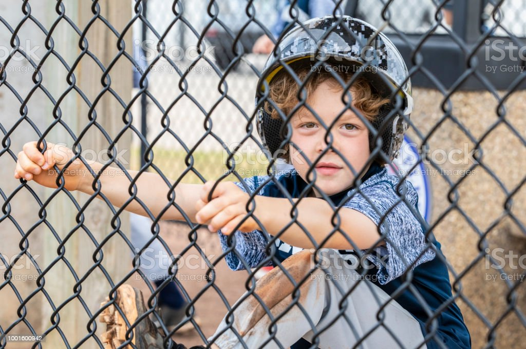 Young boy hangs out in the dugout waiting for his turn to bat at a baseball game stock photo