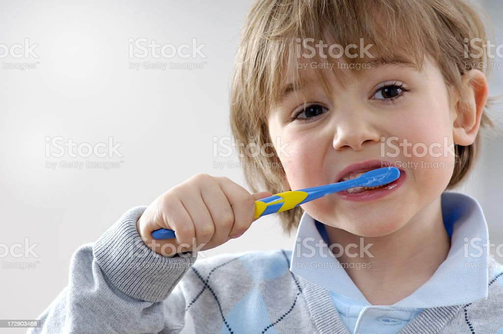 Young boy happily brushing his teeth royalty-free stock photo