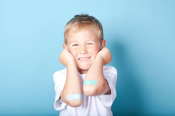 Young boy happily showing of the bandages on his elbows stock photo