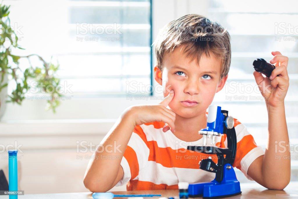 kleiner Junge hat eine Idee bei der Arbeit mit dem Mikroskop – Foto