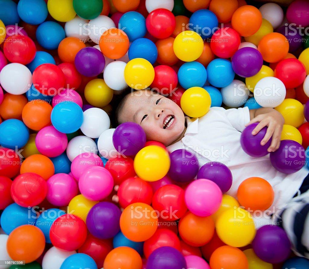 A young boy having fun in a ball pool stock photo