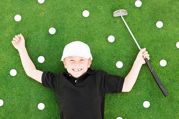 Young Boy Having Fun On Golf Course stock photo