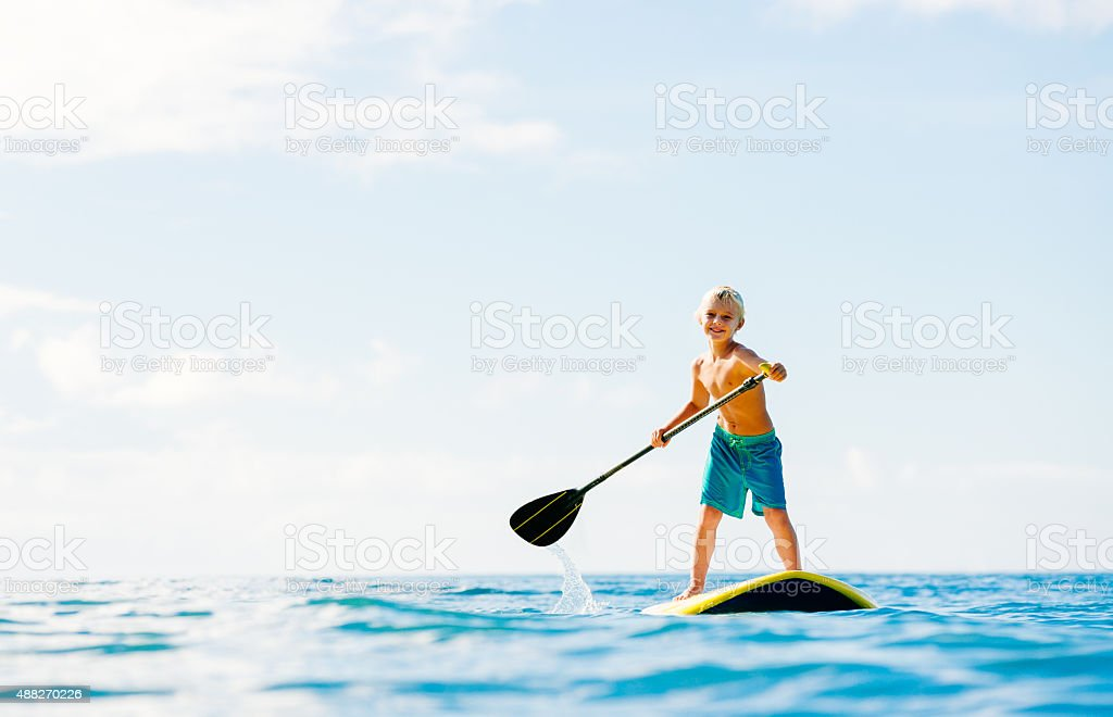 Young Boy Having Fun Stand Up Paddling stock photo