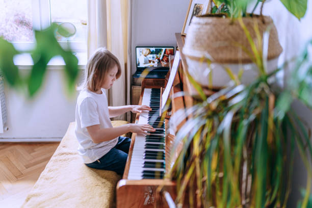 Young boy having online piano class. Home education. stock photo
