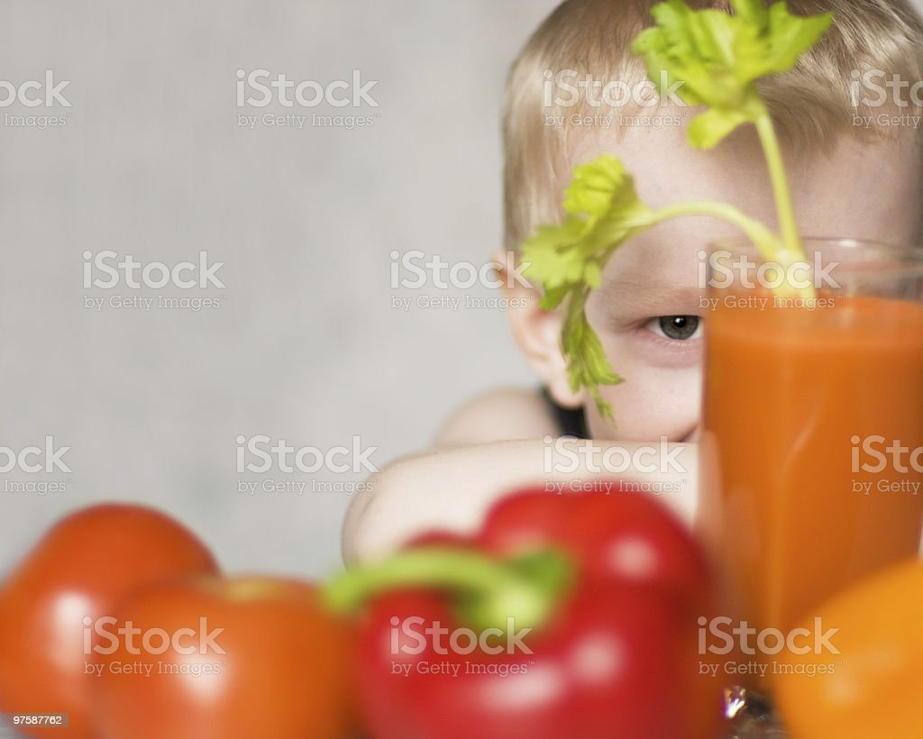 young boy hiding among vegetables royalty-free stock photo