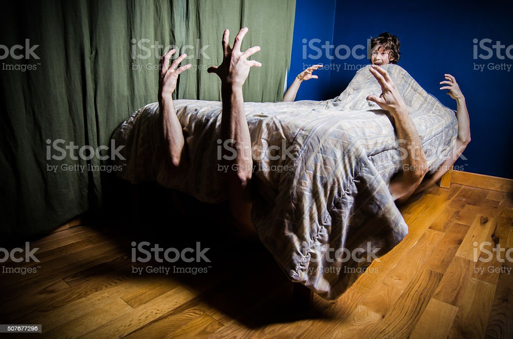 Young boy hiding in bed with monsters under bed stock photo