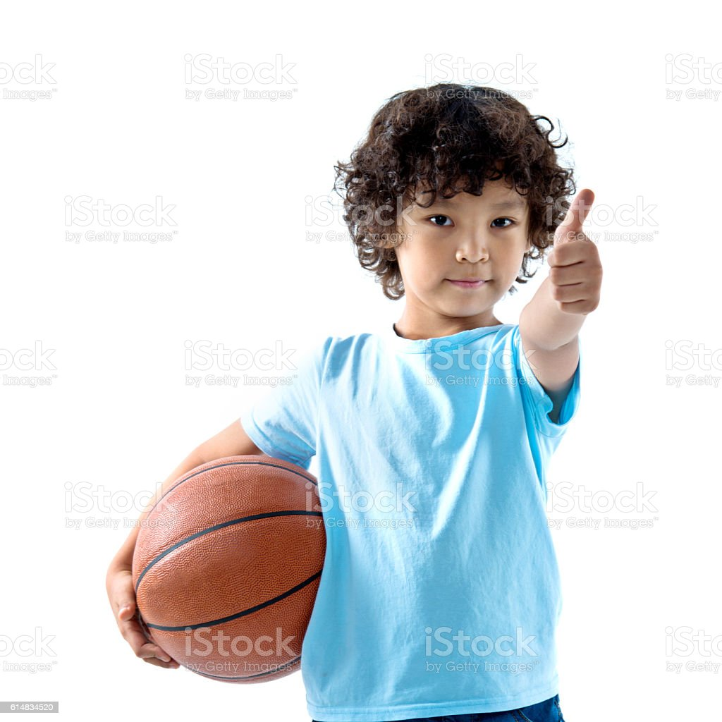Young boy holding a basketball against white background stock photo