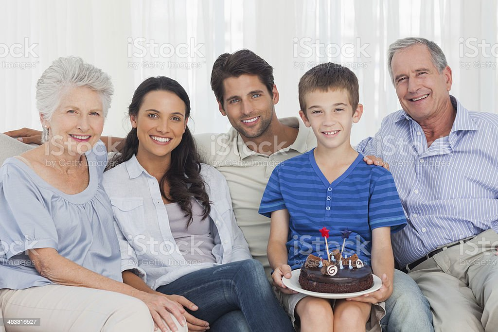 Young boy holding a birthday cake sitting on couch royalty-free stock photo