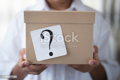 young boy holding a box with white note question mark. concept of suprise and gift