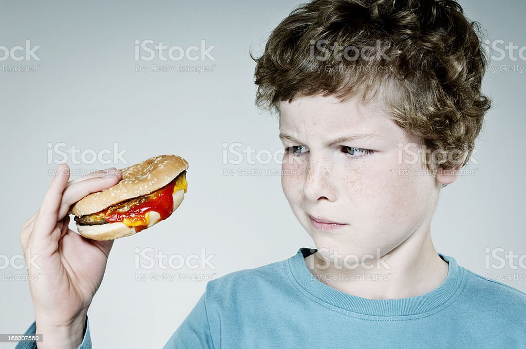 A young boy holding a burger staring at it royalty-free stock photo