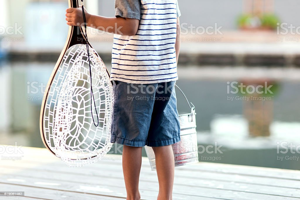 Young boy holding fishing net and catch pale royalty-free stock photo