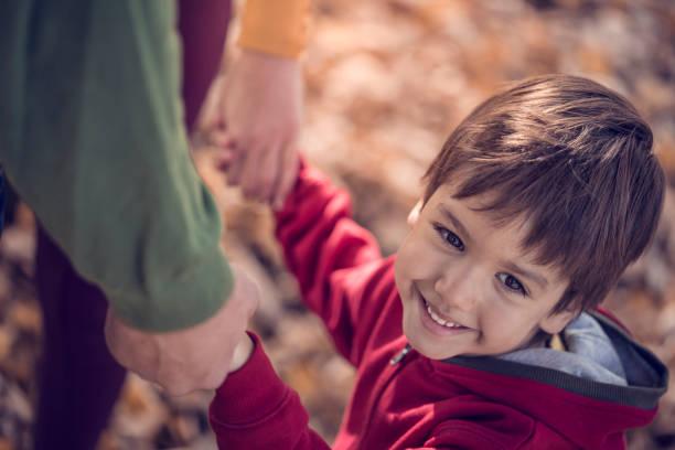 Kleiner Junge Hand in Hand mit seiner Mutter und seinem Vater im park – Foto