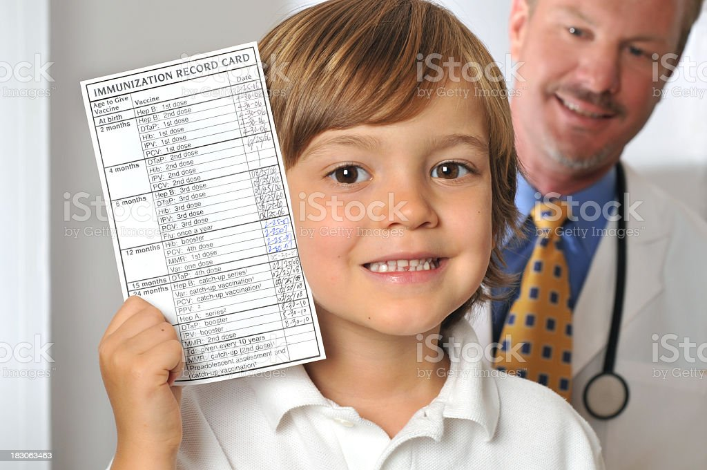 Young Boy Holding Immunization Record in Doctor's Office stock photo