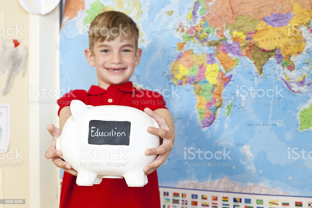 Young Boy Holding Out Piggy Bank For Education stock photo