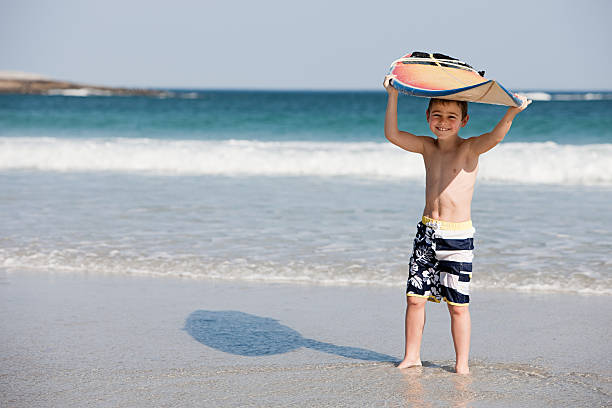 Young boy holding surfboard above head at the edge of the sea stock photo