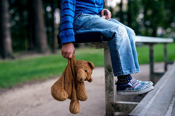 young boy holding teddybear while alone on the bleachers - häusliche gewalt stock-fotos und bilder