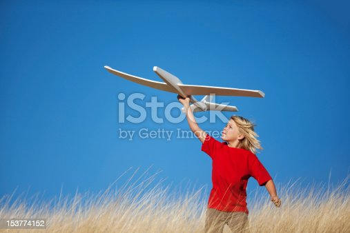 9-yr old male standing in grassy field about to fly a model airplane.