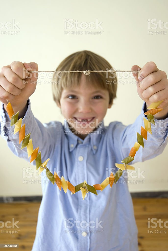 A young boy holding up a macaroni necklace royalty-free stock photo
