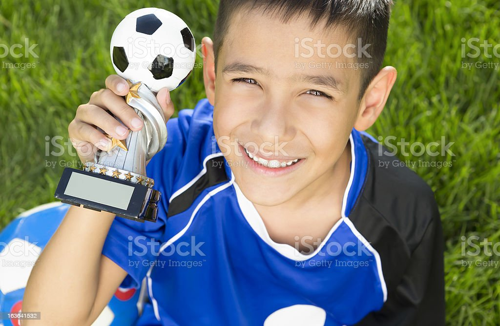 Young boy holding up his soccer trophy royalty-free stock photo