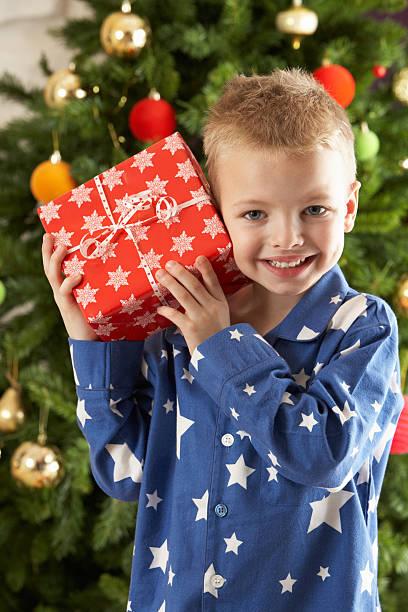 Junge Holding eingewickelt Geschenk vor Weihnachten Baum – Foto