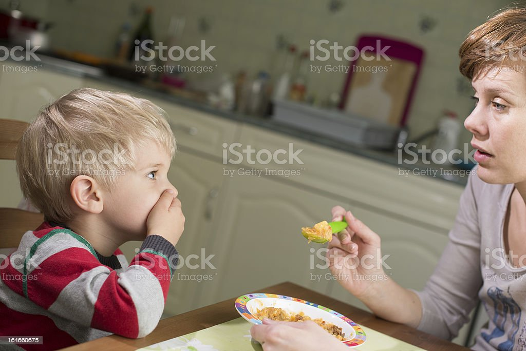 Young boy holds hand on his mouth to stop eating stock photo