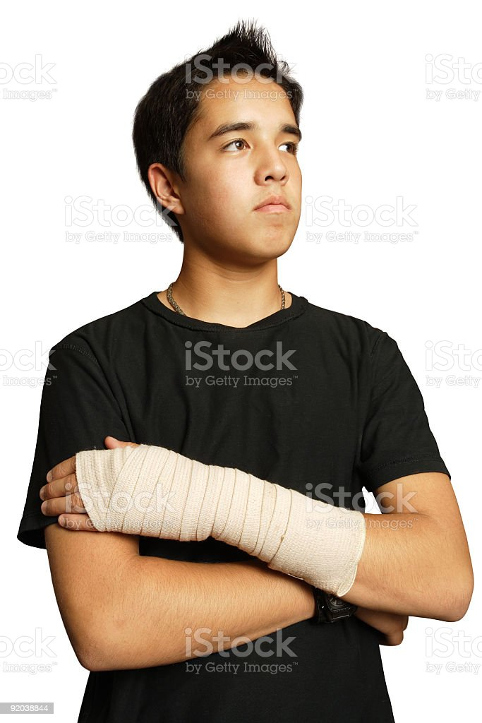 A young boy holds his sprained wrist against himself  stock photo