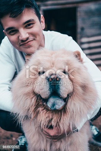 istock Young Boy Hugging his Chow Chow Dog Outdoors 944920252