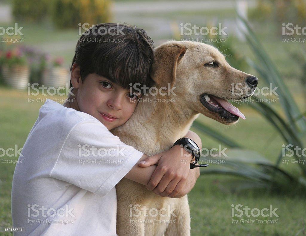 Young boy hugs his yellow Laborador dog outside royalty-free stock photo