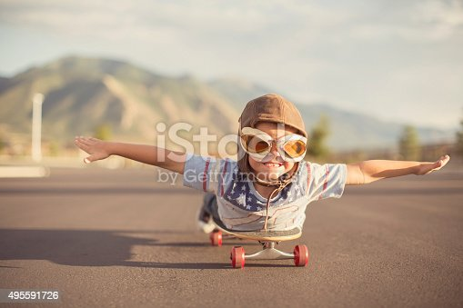 istock Young Boy Imagines Flying On Skateboard 495591726