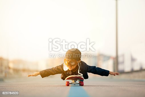 istock Young Boy Imagines Flying On Skateboard 625784520