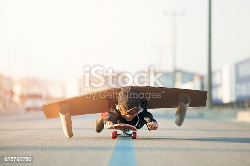 istock Young Boy Imagines Flying On Skateboard 625793780
