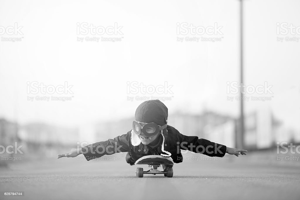 Young Boy Imagines Flying On Skateboard stock photo