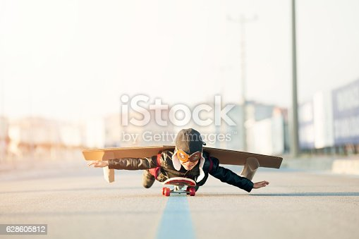 istock Young Boy Imagines Flying On Skateboard 628605812