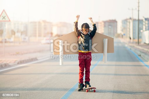 istock Young Boy Imagines Flying On Skateboard 628606194